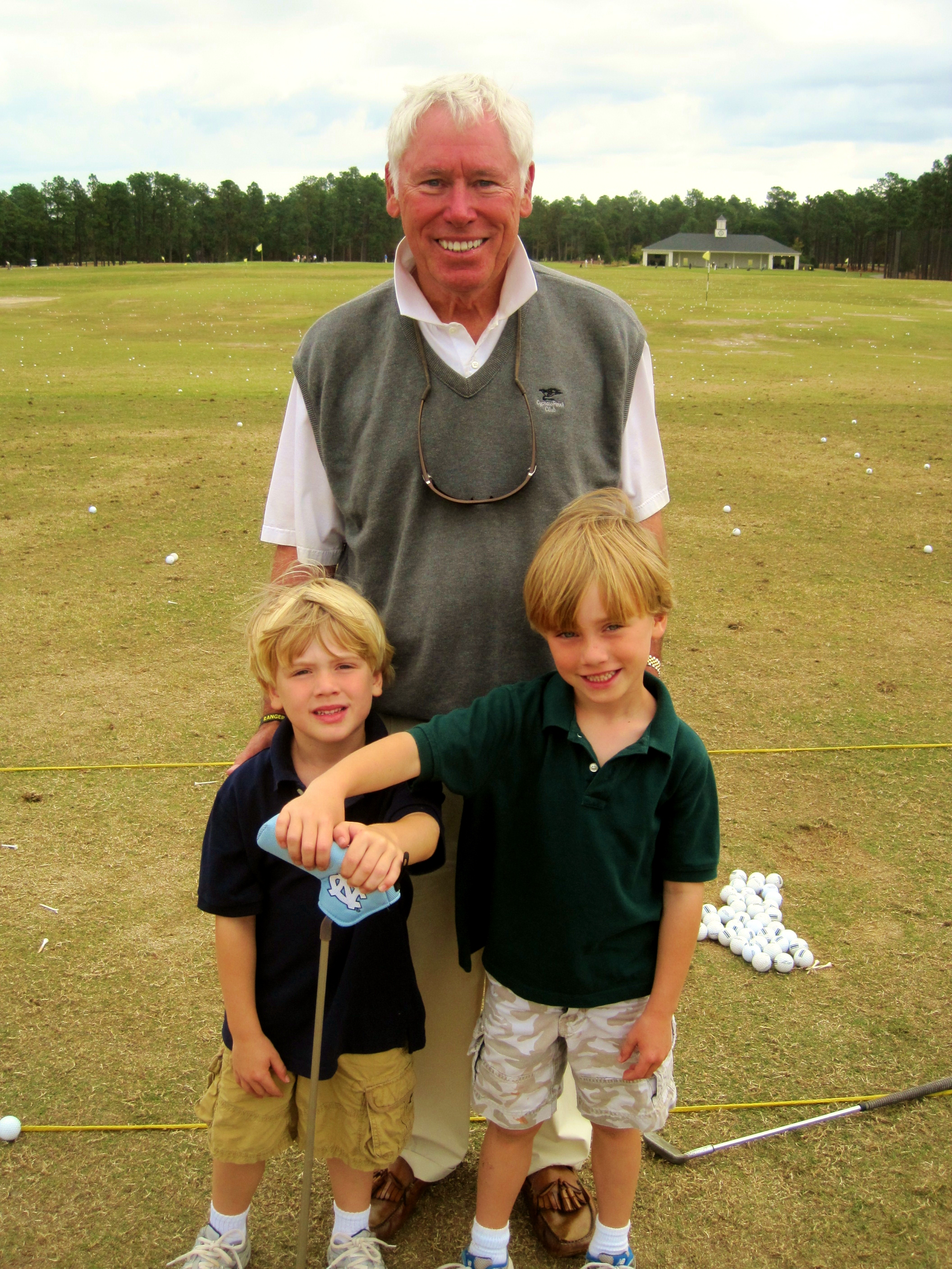 Pinehurst member Joe McAuley stands with his grandsons Porter 4, (left) and McAuley, 6, (right) on the practice range at Pinehurst Resort.