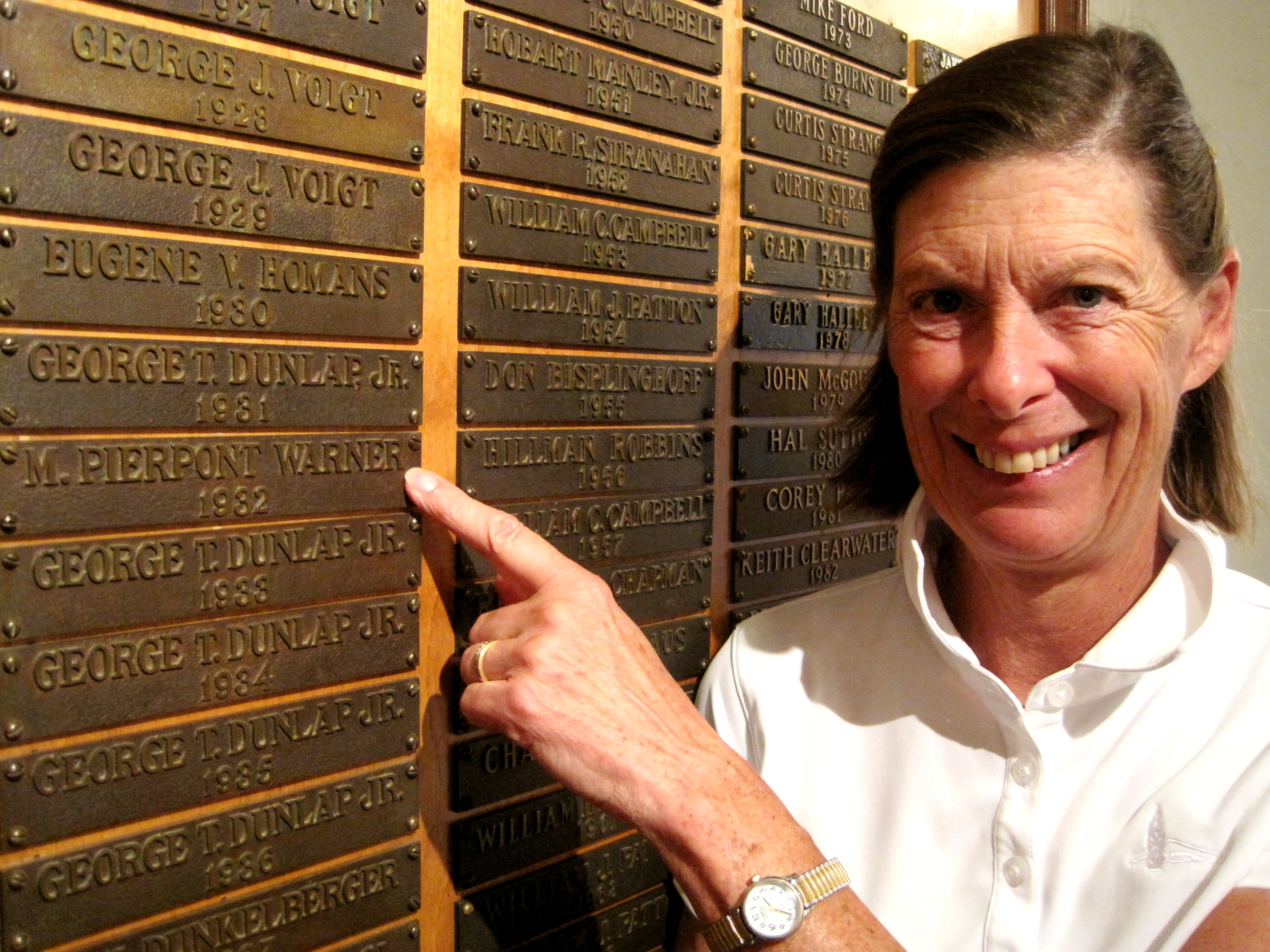 Lili Geehr points to her father's name, M. Pierpont Warner, on the North and South Amateur Champion Wall of Perpetuity at Pinehurst Resort.