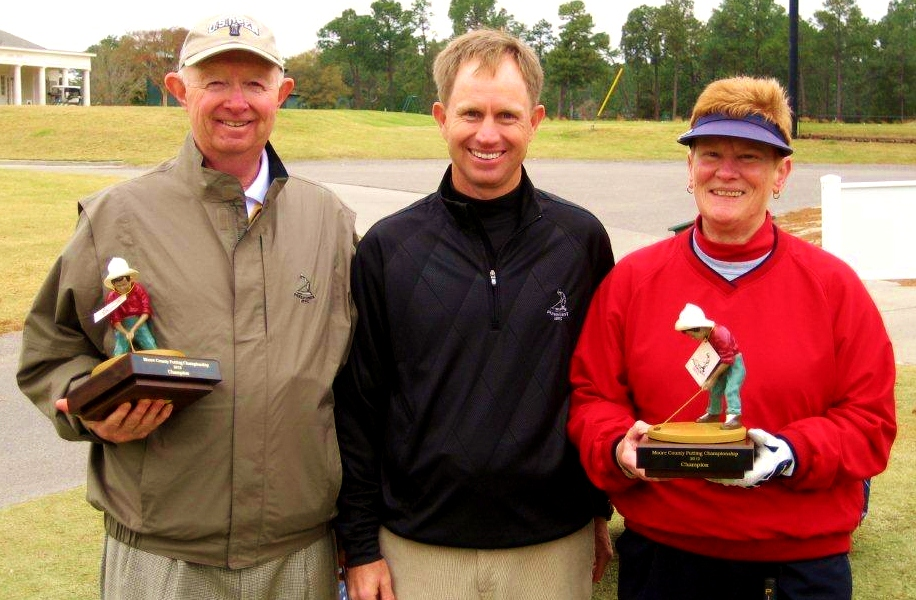 Pinehurst President Don Padgett II (left) and Nancy Barnes (right) won the men's and women's divisions of the inaugural Moore County Putting Championship at Pinehurst Resort's Thistle Dhu. Kelly Mitchum (center), who helped organize the event, joins them.