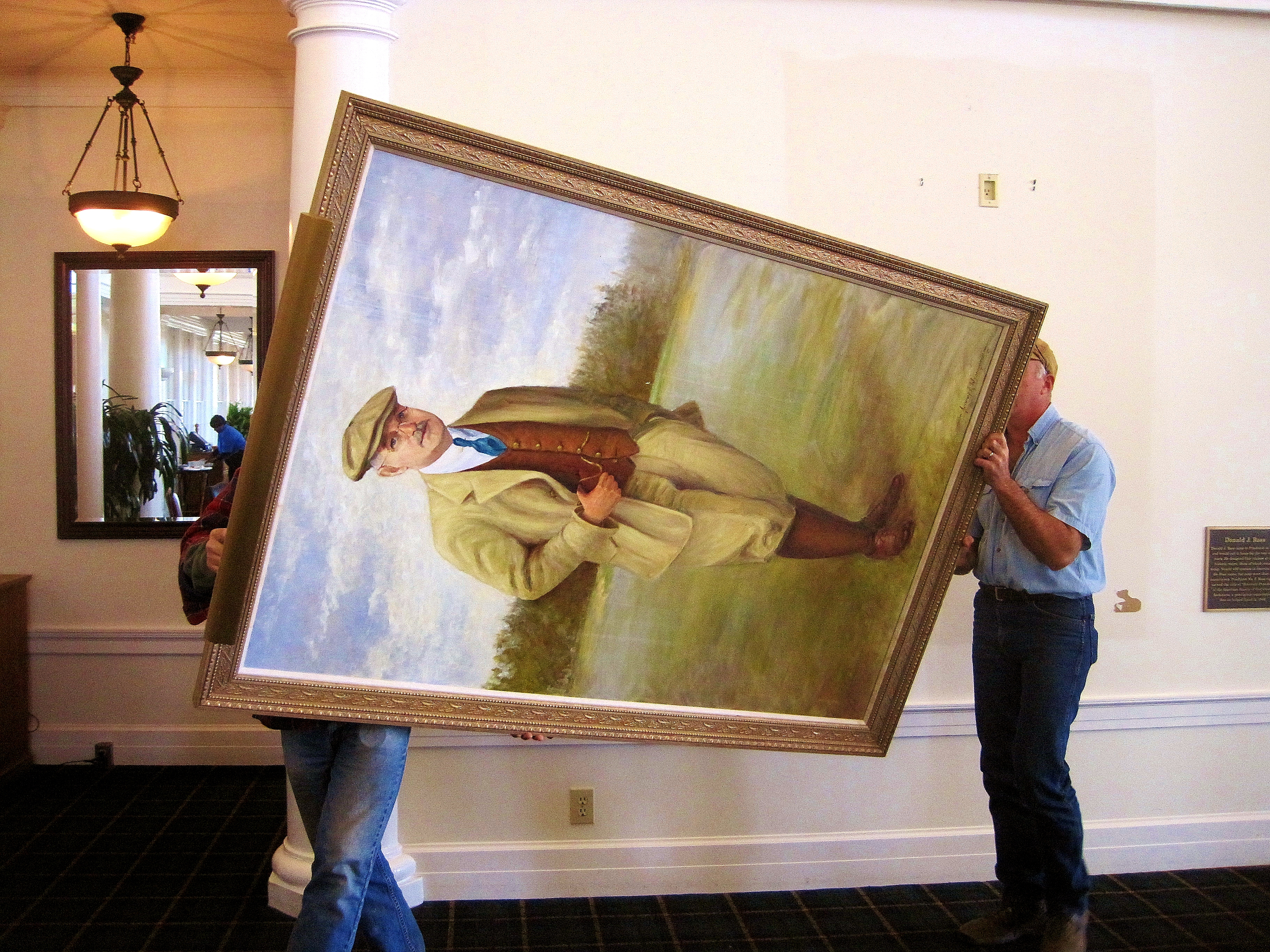 Art Conservator Shane Bufmeyer (right) and an assistant remove the Donald Ross portrait from Pinehurst's Resort Club on Thursday. The portrait will be restored this month.